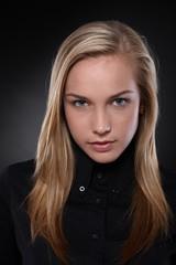 Unsmiling, blonde teenager in black