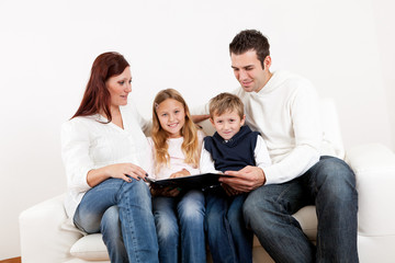 Hapy young family watching photo album