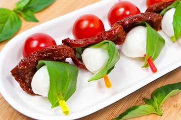 Canapes with cherry tomato, mozzarella, dried tomatoes and basil