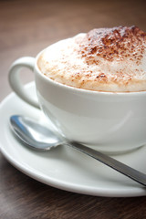 A cup of Cappuccino with a spoon
