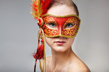 Portrait of beautiful young woman wearing red carnival mask