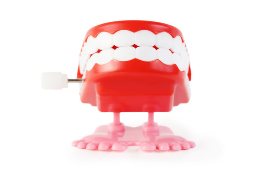bright toy clockwork jaw with white teeth on pink legs