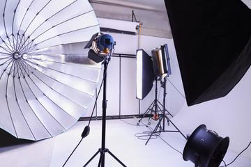 Empty photo studio with many modern lighting equipment