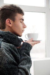 Portrait of a young man drinking coffee with his eyes closed