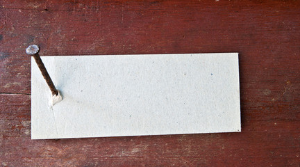 Paper label attached on wood wall with nail