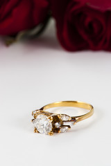 Golden diamond ring and rose on white background