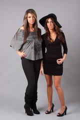 Two beautiful women wearing black outfits.