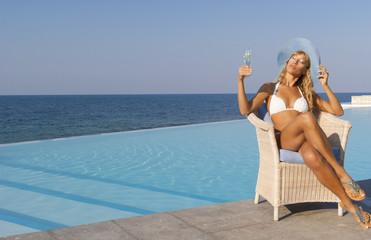 Woman in white bikini relax near infinity pool