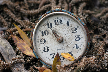 An old antique broken clock lying on the ground