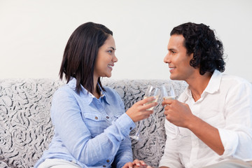 Couple having sparkling wine on the couch