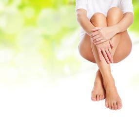 female legs being massaged over green spring background