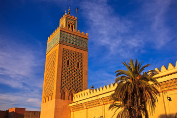 Ornate minaret rises from mosque walls into blue sky in Morocco
