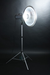 Studio flash with beauty dish on grey background