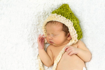Newborn Baby Sleeping with knitted Hat on.