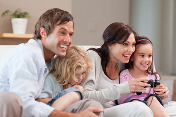 Delighted family playing video games together