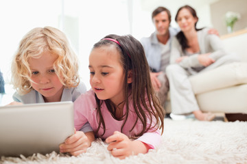 Cute siblings using a tablet computer while their parents are in