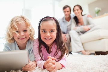 Siblings using a tablet computer while their parents are in the