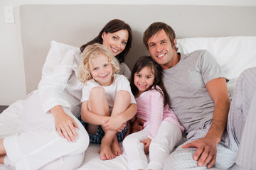 Smiling family posing on a bed