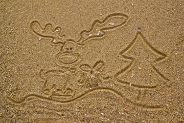 Reindeer, gift and christmas tree drawn on sand