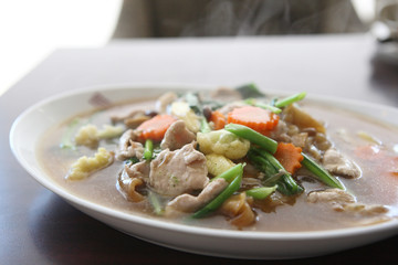 Thai food Wide Noodles in a Creamy Sauce with pork