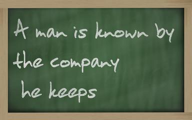 """ A man is known by the company he keeps "" written on a blackboa"