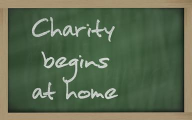 """ Charity begins at home "" written on a blackboard"
