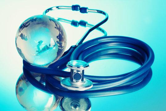 Globe and stethoscope on blue.