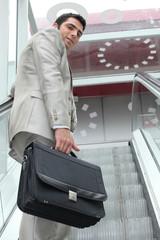 executive climbing escalator