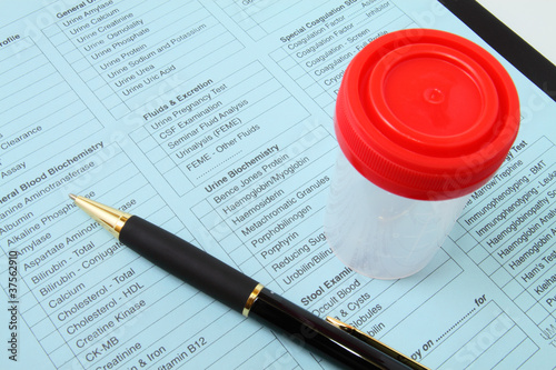Urine container and pen on lab test form