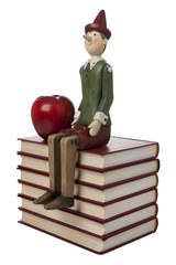 puppet with apple on pile of books