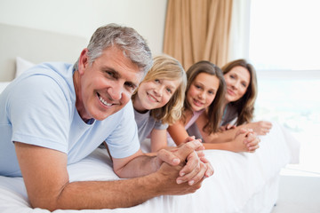 Smiling family lying on the bed