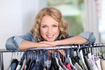 Portrait of blond woman leaning on clothes hanger