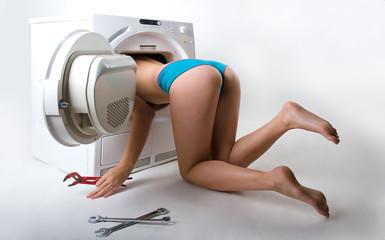Frau repariert Waschmaschine