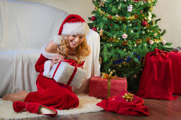 Beautiful woman in red enjoying christmas present