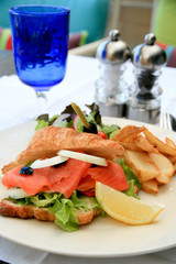 Croissant sandwich with smoked salmon, salad and home-cut fries.