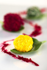Pumpkin, beetroot, spinach coconut balls on basil leaves