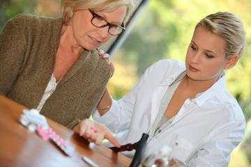 Daughter helping mother take medication