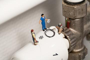 Miniatur Klempner reparieren ein Thermostat.
