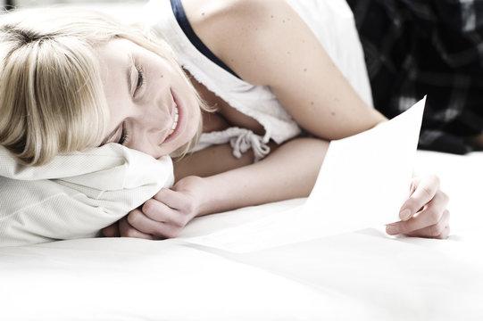 junge Frau auf Bett liest Brief