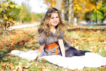 The young beautiful girl in autumn wood sits on a white plaid