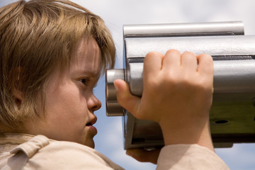 A girl with Down syndrome looking through tourist binoculars.