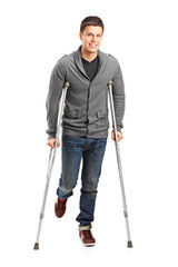 Full length portrait of an injured young man on crutches