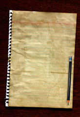 Old paper with pencil on dark wood background