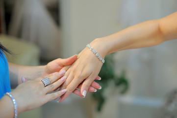 Bridesmate helps to wear a bracelet