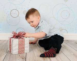 adorable toddler curious about a christmas present