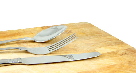 knife, fork and spoon on wooden board