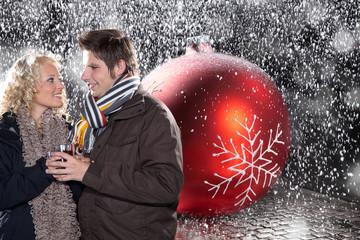 Junges verliebtes Pärchen mit Weihnachts Kugel im Schnee