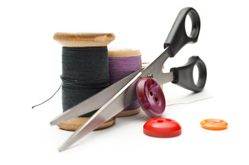 Thread bobbin, scissors and buttons on white