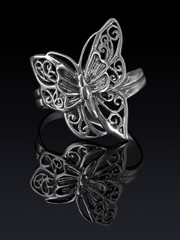 Silver ring butterfly shaped with reflection.
