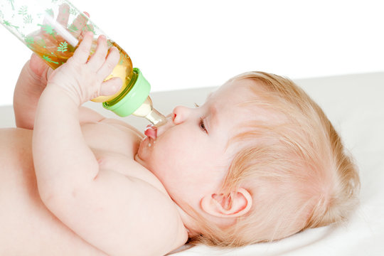 adorable child drinking from bottle. 6 months old girl.